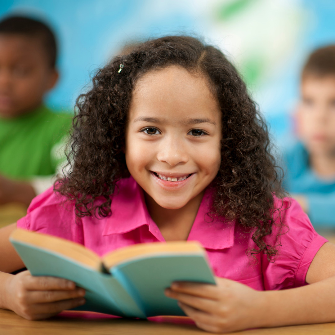 smiling elementary school child reading