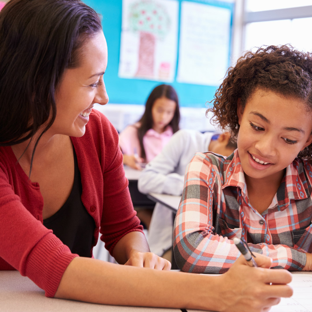 intermediate school teacher working with student